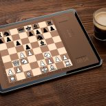 Digital tablet with chess app on screen on dark background