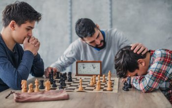 Two young boys and their mentor adult man, playing chess in school of chess.