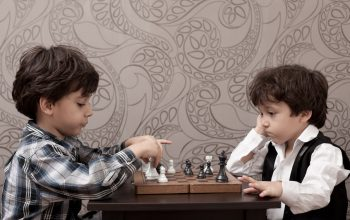 Two little boys playing chess at home in front of wallpapered background.